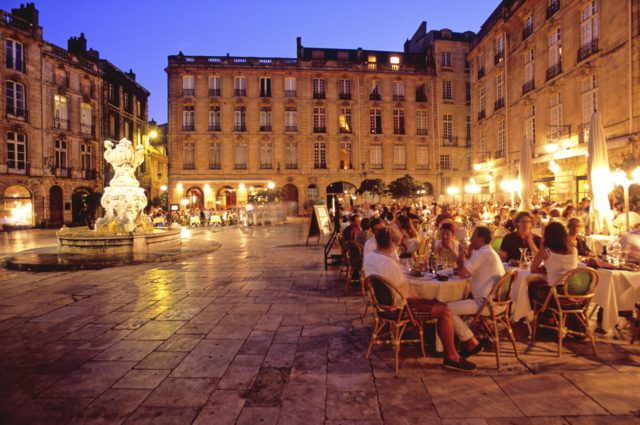 IMAGE: Photo showing a square in Bordeaux at dusk with people having dinner